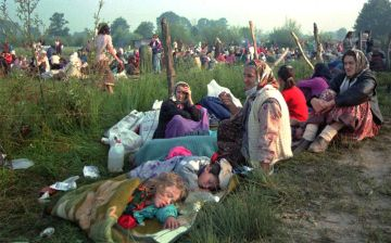 FILE - A July 14, 1995 file photo shows refugees from the overrun U.N. safe haven enclave of Srebrenica who had spent the night outdoors, gathering outside the U.N. base at Tuzla airport. More than 20 years after Bosnia's war, Radovan Karadzic will learn his fate on Thursday when U.N. judges deliver verdicts in his genocide and war crimes trial. (AP Photo/Darko Bandic, File)