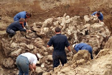 International forensic experts examine dozens of bodies, believed to be some of the 8000 missing persons who fled Srebrenica in July 1995, in a mass grave in the Serb entity of Pilicer, Bosnia in a September 18, 1996 file photo. Bosnian Serb wartime general Ratko Mladic was arrested in Serbia on May 26, 2011 after years on the run from international genocide charges, opening the way for the once-pariah state to approach the European mainstream. Mladic, accused of orchestrating the massacre of 8,000 Muslim men and boys in the town of Srebrenica and a brutal 43-month siege of Sarajevo during Bosnia's 1992-5 war, was found in a farmhouse owned by a cousin, a police official said. REUTERS/Kevin Coombs/files  (BOSNIA - Tags: CIVIL UNREST CRIME LAW)