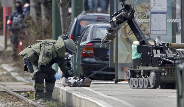 Un agente belga de desactivación de explosivos y un robot inspeccionan la mochila de un sospechoso que minutos antes había sido herido por la policía en Schaerbeek , Bruselas. (Reuters)