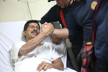 Pablo Rafael Cordova Ca?izares shakes hands with one of the Colombian firefighters who rescued him, at the Verdi Cevallos Balda hospital in Portoviejo, Ecuador, Monday, April 18, 2016. The 51-year-old hotel administrator was one of a trickle of survivors pulled from the rubble after Ecuador's strongest earthquake in decades flattened towns along the coast and killed hundreds. (AP Photo/Emilio D. Garcia)