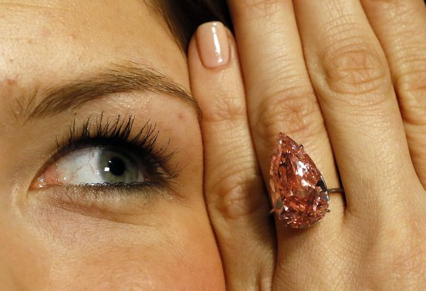 FILE - In this April 7, 2016 file picture a  model displays 'The Unique Pink' the largest Fancy Vivid Pink pear shaped diamond ever offered at auction, at Sotheby's auction rooms in London.  The diamond is expected to realize 28-38 million US dollars when is goes for auction in Geneva on Tuesday  May 17. (AP Photo/Kirsty Wigglesworth,file)