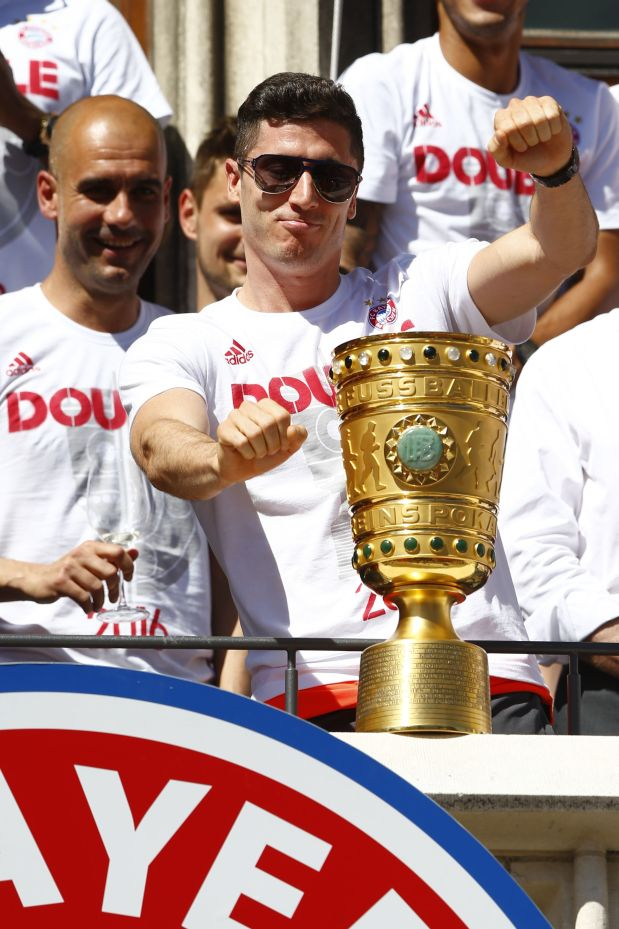 Bayern's Robert Lewandowski celebrates behind the German soccer cup trophy on the balcony of the town hall at Marienplatz square in Munich, Germany, Sunday, May 22, 2016. (AP Photo/Matthias Schrader)