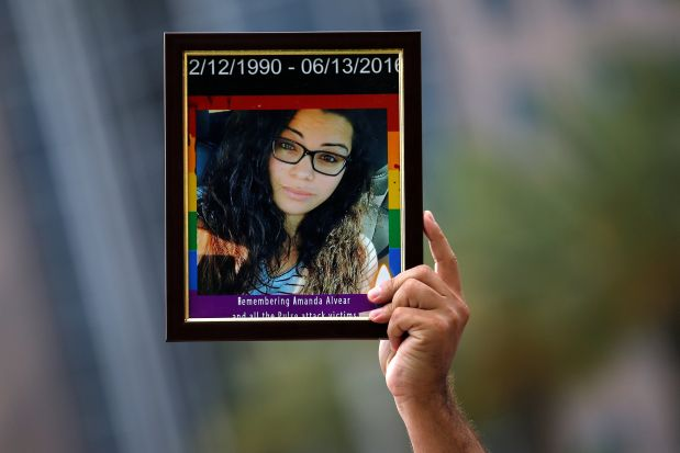A friend of Amanda Alvear holds up her photo at a memorial service the day after a mass shooting at the Pulse gay nightclub in Orlando, Florida, U.S. June 13, 2016. REUTERS/Carlo Allegri