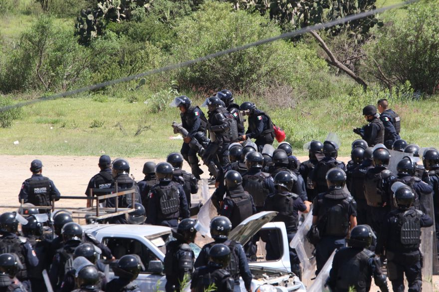 Riot police carry away an injured officer as they battle with protesting teachers who were blocking a federal highway in the state of Oaxaca, near the town of Nochixtlan, Mexico, Sunday, June 19, 2016. The teachers are protesting against plans to overhaul the country's education system which include federally mandated teacher evaluations.(AP Photo/Luis Alberto Cruz Hernandez)