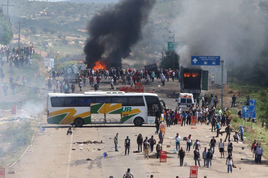 Protesting teachers who were blocking a federal highway hold their positions with a passenger bus across the road and burning trucks as they battle with riot police in the state of Oaxaca, near the town of Nochixtlan, Mexico, Sunday, June 19, 2016. The teachers are protesting against plans to overhaul the country's education system which include federally mandated teacher evaluations.(AP Photo/Luis Alberto Cruz Hernandez)