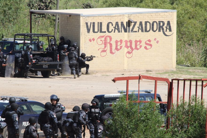 Riot police use a rifle as they battle with protesting teachers who were blocking a federal highway in the state of Oaxaca, near the town of Nochixtlan, Mexico, Sunday, June 19, 2016. The teachers are protesting against plans to overhaul the country's education system which include federally mandated teacher evaluations. (AP Photo/Luis Alberto Cruz Hernandez)