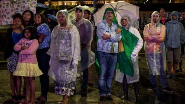 La lluvia no fue obstáculo para que varios disfrutaran de los fuegos artificiales desde afuera del estadio, aunque no pudieron ocultar su sensación de incertidumbre. (Foto: BBC)