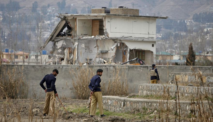 Policemen stand guard near the partially demolished compound where al Qaeda leader Osama bin Laden was killed by U.S. special forces last May, in Abbottabad this February 26, 2012 file photo. Al Qaeda's leaders were increasingly worried about spies in their midst, drones in the air and secret tracking devices reporting their movements as the U.S.-led war against them grinds on, documents seized in the 2011 raid on Osama bin Laden's Pakistani hideout and obtained by Reuters reveal.  REUTERS/Faisal Mahmood/Files