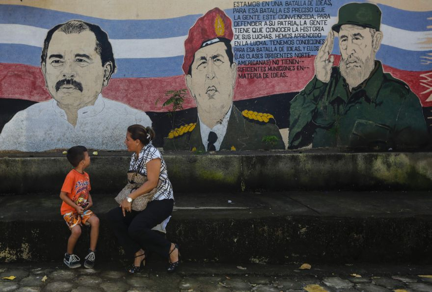 A woman and child sit on a bench in front of a mural depicting Nicaragua's President Daniel Ortega (L), late Venezuela's President Hugo Chavez (C) and former Cuba's President Fidel Castro in Managua on November 4, 2016 head of Sunday's general elections. Ortega looks to be heading for an easy re-election to a fourth term this weekend, with his wife as his running mate. Surveys credit the pair with more than 60 percent voter support for Sunday's balloting, far ahead of their rivals. But critics inside and outside the country are calling foul over tactics that have sidelined the opposition and restricted foreign scrutiny. / AFP / INTI OCON