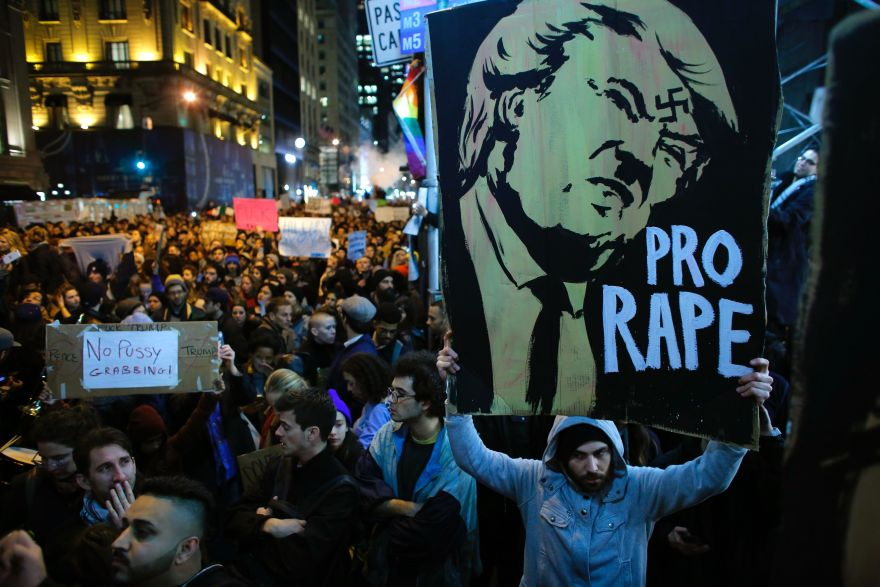A man holds a poster as she takes part in a protest against President-elect Donald Trump in New York City on November 9, 2016. / AFP / KENA BETANCUR