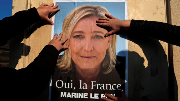 Supporters paste a poster of Marine Le Pen, France's National Front leader, on a wall before a political rally for local elections in Frejus, France March 18, 2014.REUTERS/Eric Gaillard/File Photo