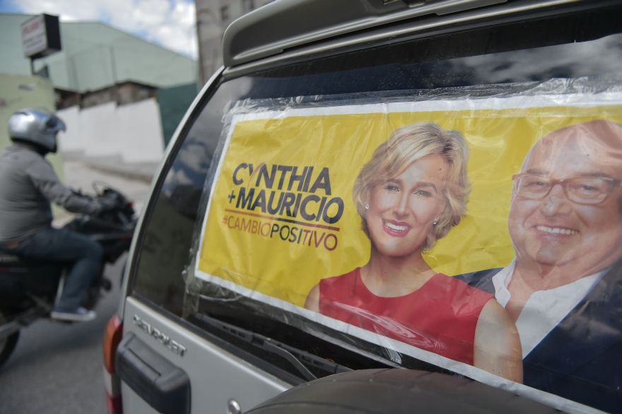 A SUV bears electoral propaganda of presidential candidate Cynthia Viteri (L) and her running mate Mauricio Pozo, in Quito on January 3, 2017 as campaigning opened for Ecuador's February 19 general elections, which will decide who succeeds leftist President Rafael Correa after a decade in power. Eight candidates are vying to replace Correa, a radical economist and one of the last of a generation of leftist leaders who dominated Latin American politics for more than a decade. The race comes at a time when the region's politics have shifted firmly to the right amid an economic downturn. / AFP / Rodrigo BUENDIA