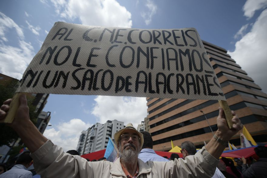A man holds a sign reading