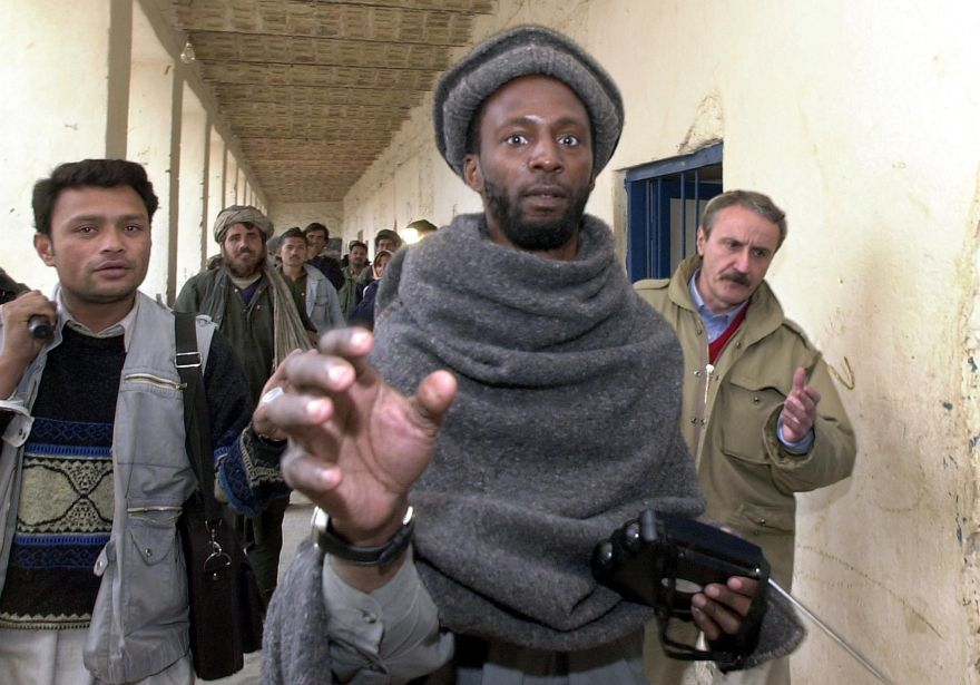 (FILES) This file photo taken on December 13, 2001 shows alleged British national from Manchester Jamal al-Harith (C), a Muslim convert of Jamaican origin who was born Ronald Fiddler, surrounded by journalists at Kandahar jail, Afghanistan.  A suicide bomber who the Islamic State group claimed detonated a suicide bomb against Iraqi forces outside Mosul was named in British media as Jamal al-Harith, who was detained at Guantanamo Bay between 2002 and 2004. / AFP / BANARAS KHAN