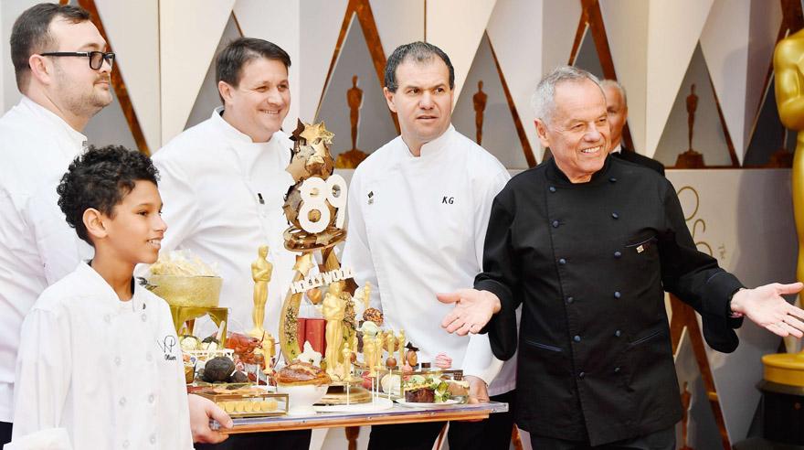 El chef Wolfgang Puck, encargado de la cena con la que se homenajeará a los ganadores del Oscar, desfila a su estilo por la alfombra roja. (Foto: AFP)
