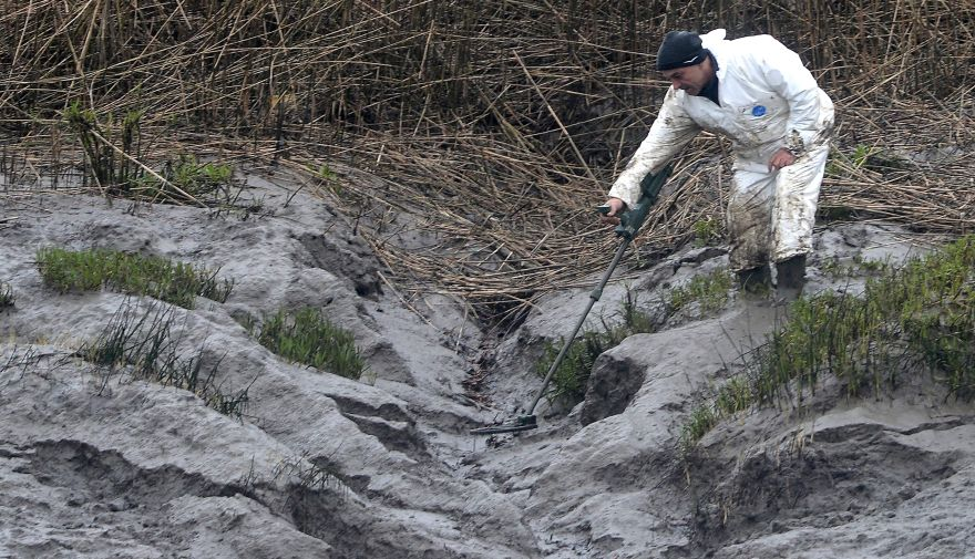 A police officer searches on March 9, 2017 on the swampy bank of the river Aulne near the Caouissin's house in Pont-de-Buis-l?s-Quimerch, western of France. Investigators on March 8, found body parts at the home in northwest France of Hubert Caouissi, the man who has confessed to killing four relatives with a crowbar, the prosecutor in the case said. The mother of Pascal Troadec, one of the four victims of Hubert Caouissin, and that of Lydie, the companion of the supposed assassin, explains that the treasure discovered by her late husband is at the origin of the tragedy, in an interview with  French newpapers Le Parisien on March 9, 2017. / AFP / FRED TANNEAU