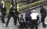 Un policía apunta un arma a un hombre en el suelo mientras los servicios de emergencia asisten en el sitio frente al Palacio de Westminster (Stefan Rousseau/PA via AP).
